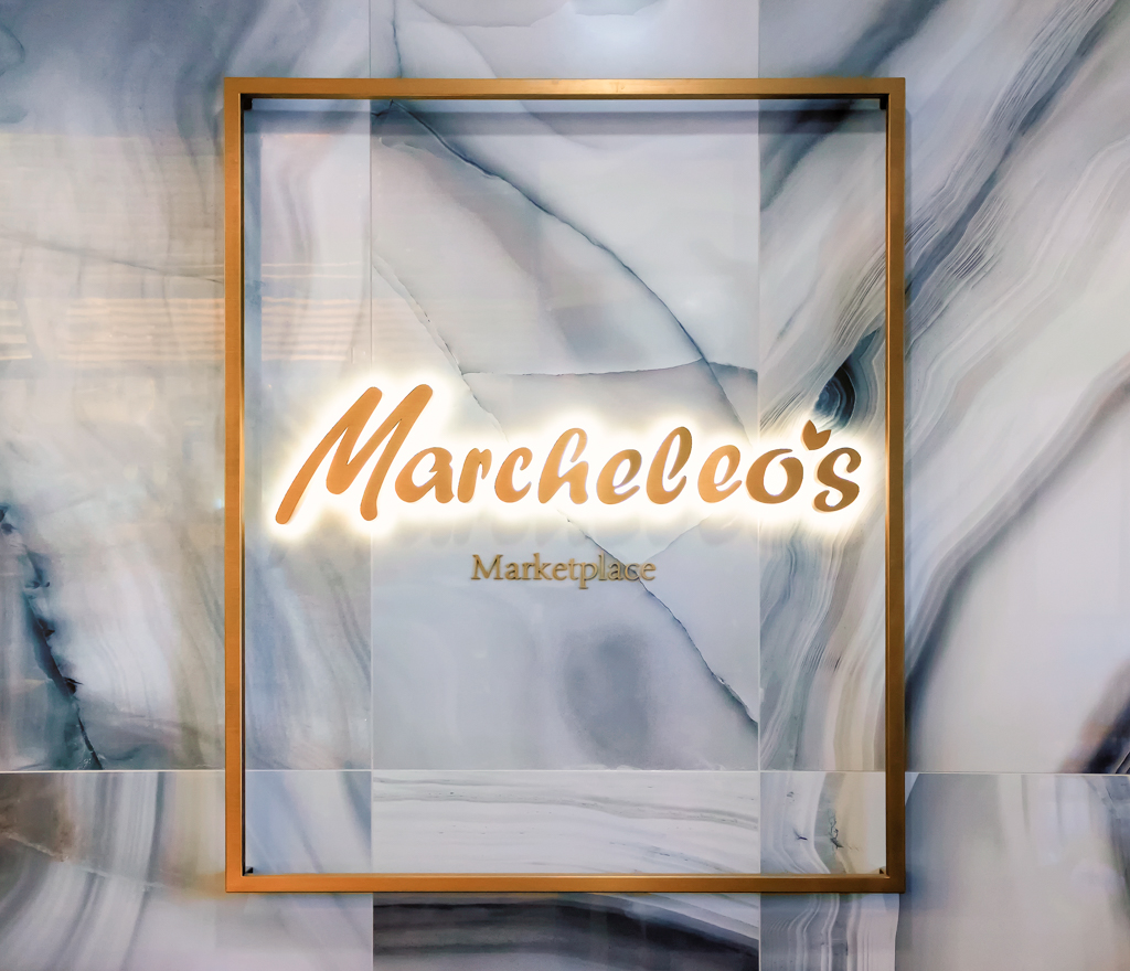 <strong>Marcheleo's Marketplace<span><b>in</b>Custom Signage </span></strong><i>→</i>